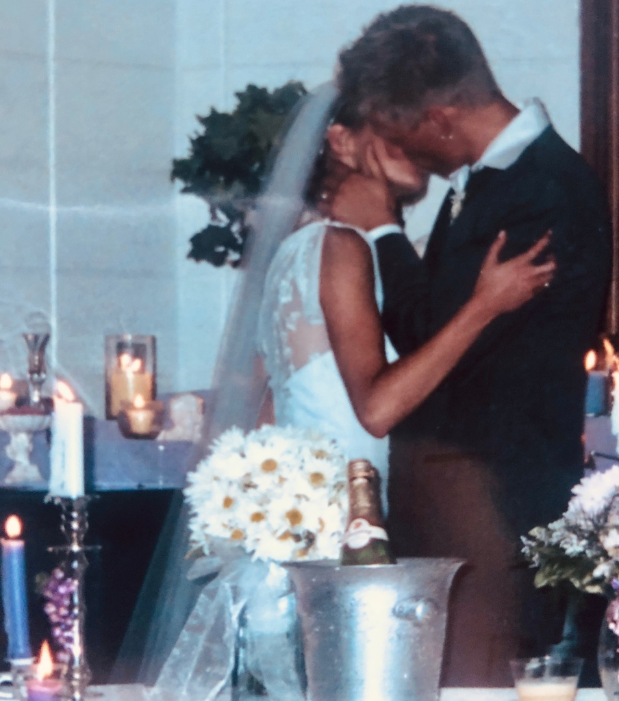 Kissing at our wedding reception over 18 years ago. We were just 19 and 21.